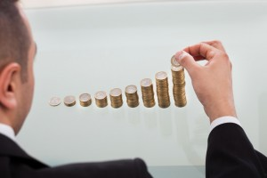 Businessman Stacking Coins In Increasing Order